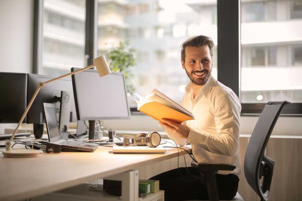A happy employee at his desk, whose company has invested in him