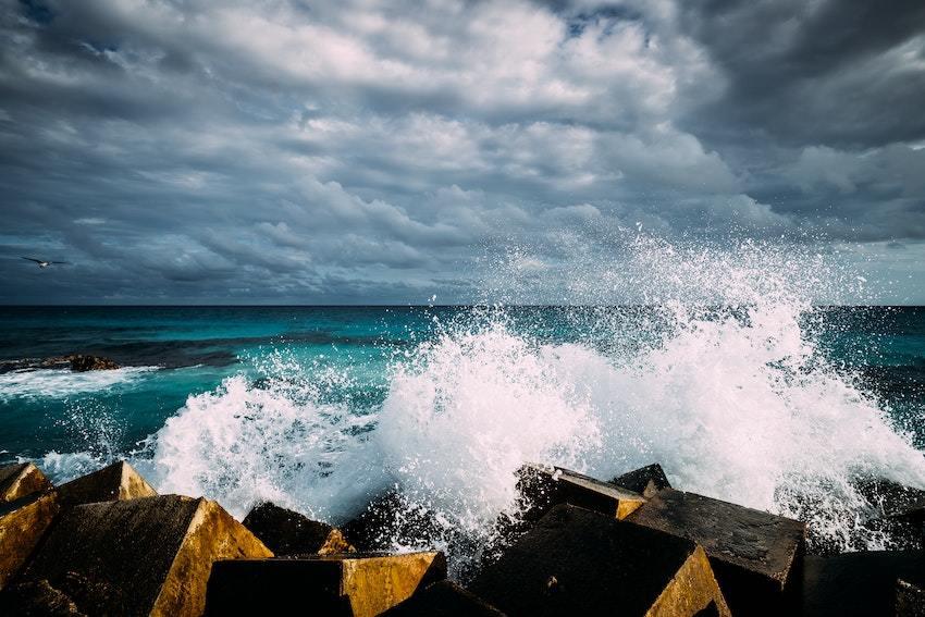 waves crashing on rocks represents the rocky shore of stock market vulnerability.