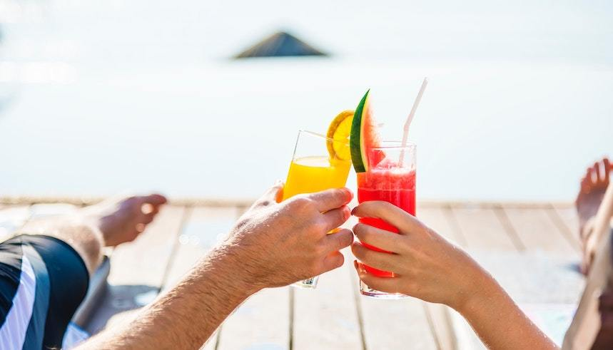 A couple clinks cocktails on a beach, signifying successful retirement planning