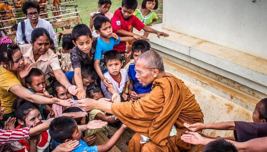 monk with children, symbolizing charitable giving