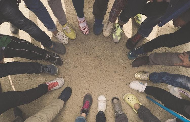 neat group of peoples legs in a circle, representing securities crowdfunding