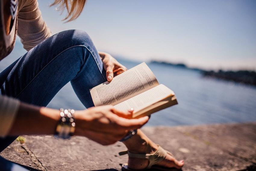 Woman reads a book lakeside, hunting for an accredited investor definition