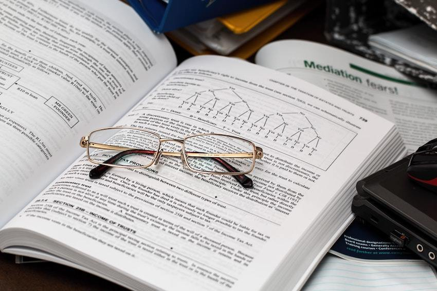 glasses resting on a textbook of accounting principles
