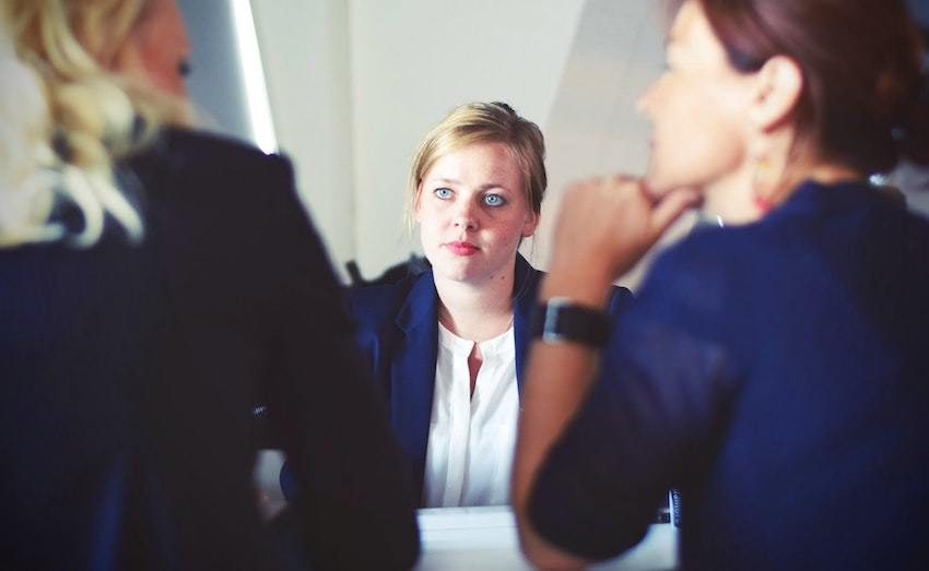 A financial advisor listens to clients in a conference room, symbolizing questions to ask a financial advisor