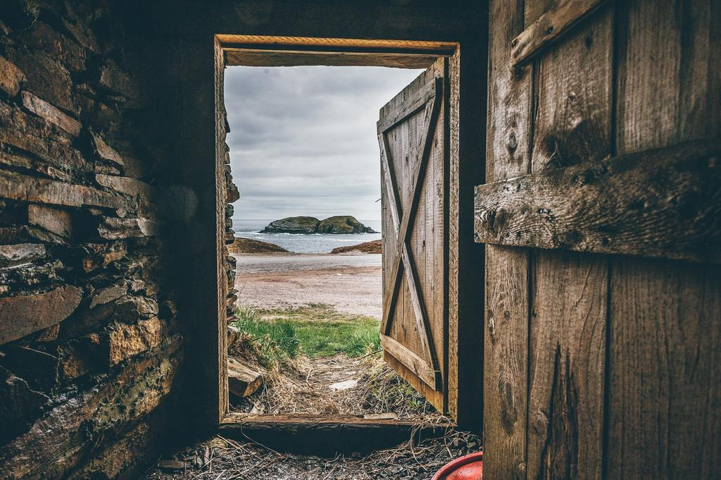 An open wooden door, representing opportunities for accredited investors in private equity