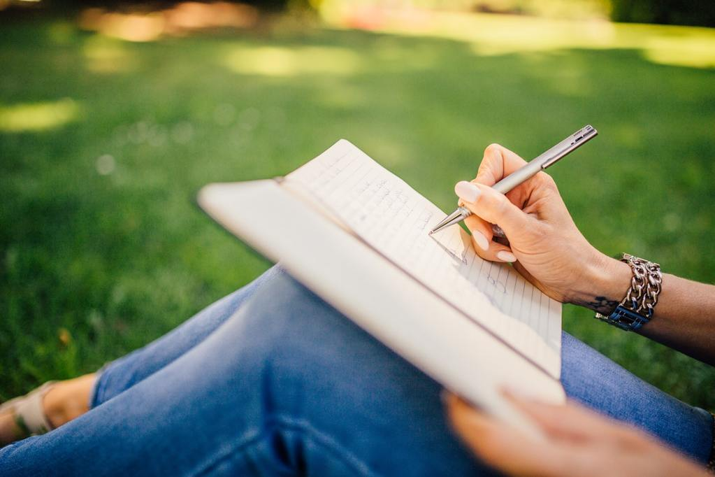 woman writes in notebook, inventing a new system of budgeting for her personal finances