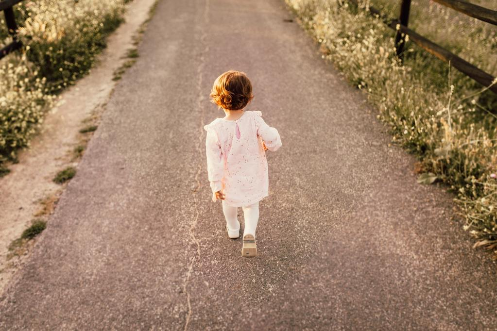 A young girl walking along a road, symbolizing first steps to financial responsibility, like how to read a credit report