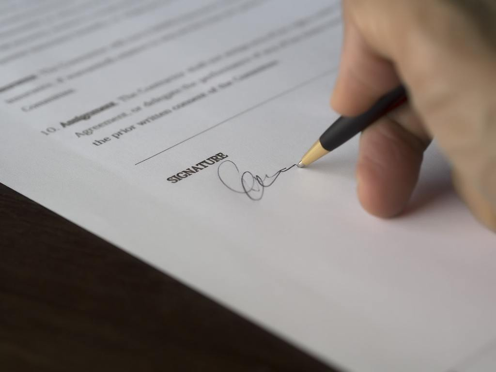 Someone's hand signs a business sale contract after finding the perfect business buyer