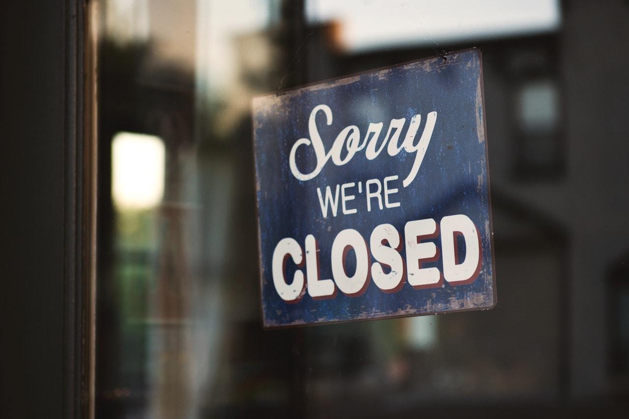 a blue and white sorry we're closed sign represents the need to apply for SBA disaster loans.