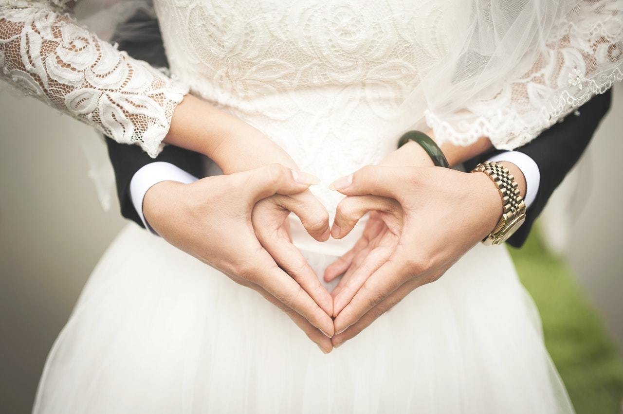 A bride and groom make heart hands, symbolizing their decision to open a joint account