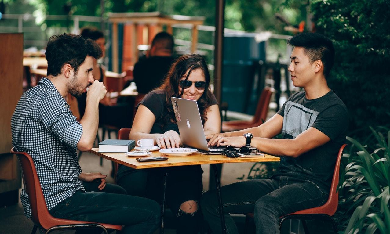 A group of Millennials programmers gather at a coffeeshop to discuss VC funding, or venture capital funding, for their startup
