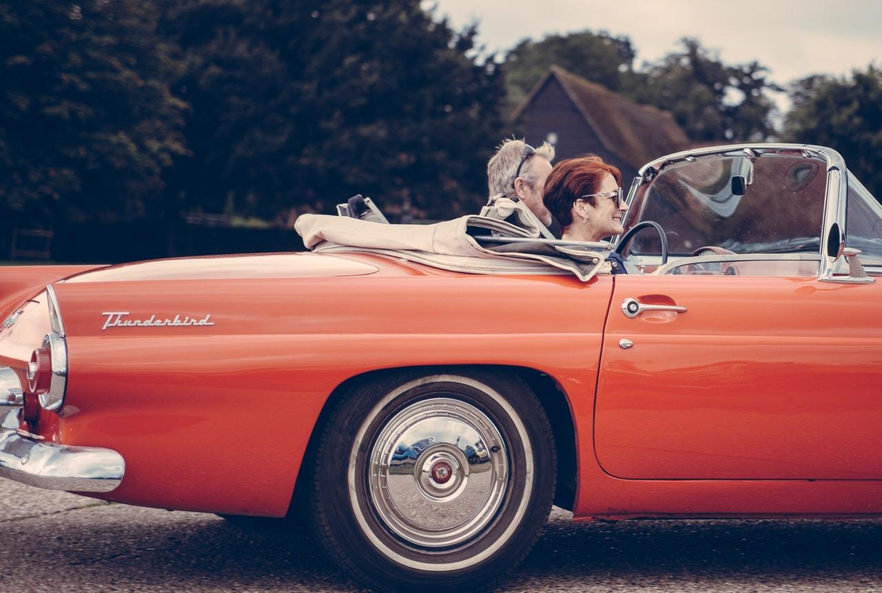 man and woman drive in red convertible, symbolizing the benefits of alternative investment ideas