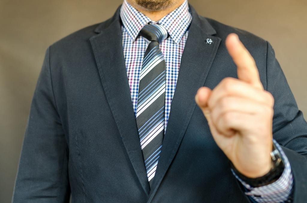 man in suit points, symbolizing leading with courage