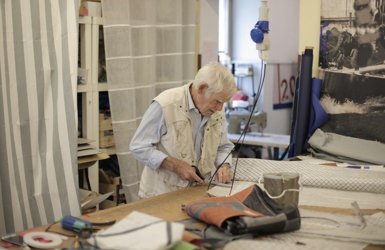 a small business owner cuts cloth and working hours in semi-retirement