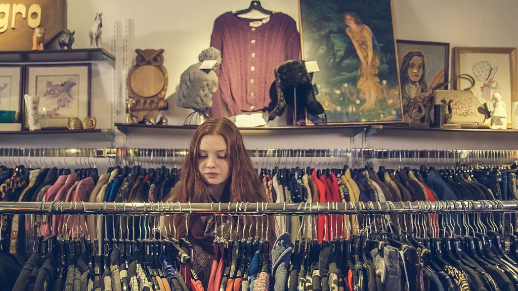 a woman shops at a second hand shop, embodying budgeting tips an frugal living