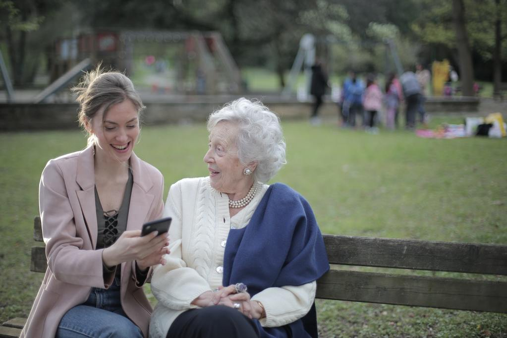 An elderly woman and her granddaughter excitedly examine their stock portfolios on the granddaughter's phone, as they discuss tax strategy and variable annuities