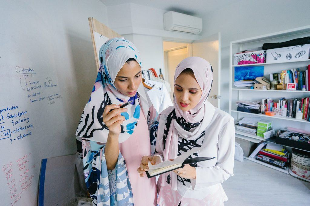 two businesswomen in headscarves are starting an LLC and learning about LLC management