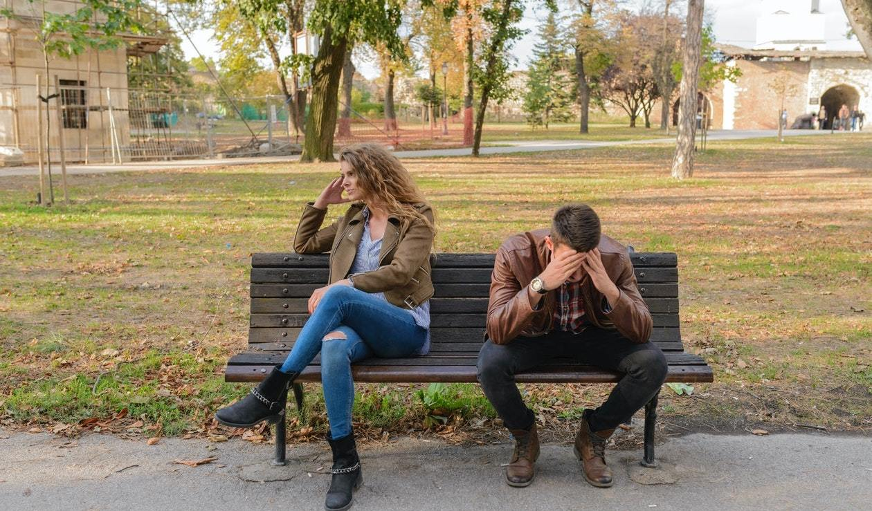 a man and a woman sit on a park bench, in an obvious fight, representing splitting assets in divorce