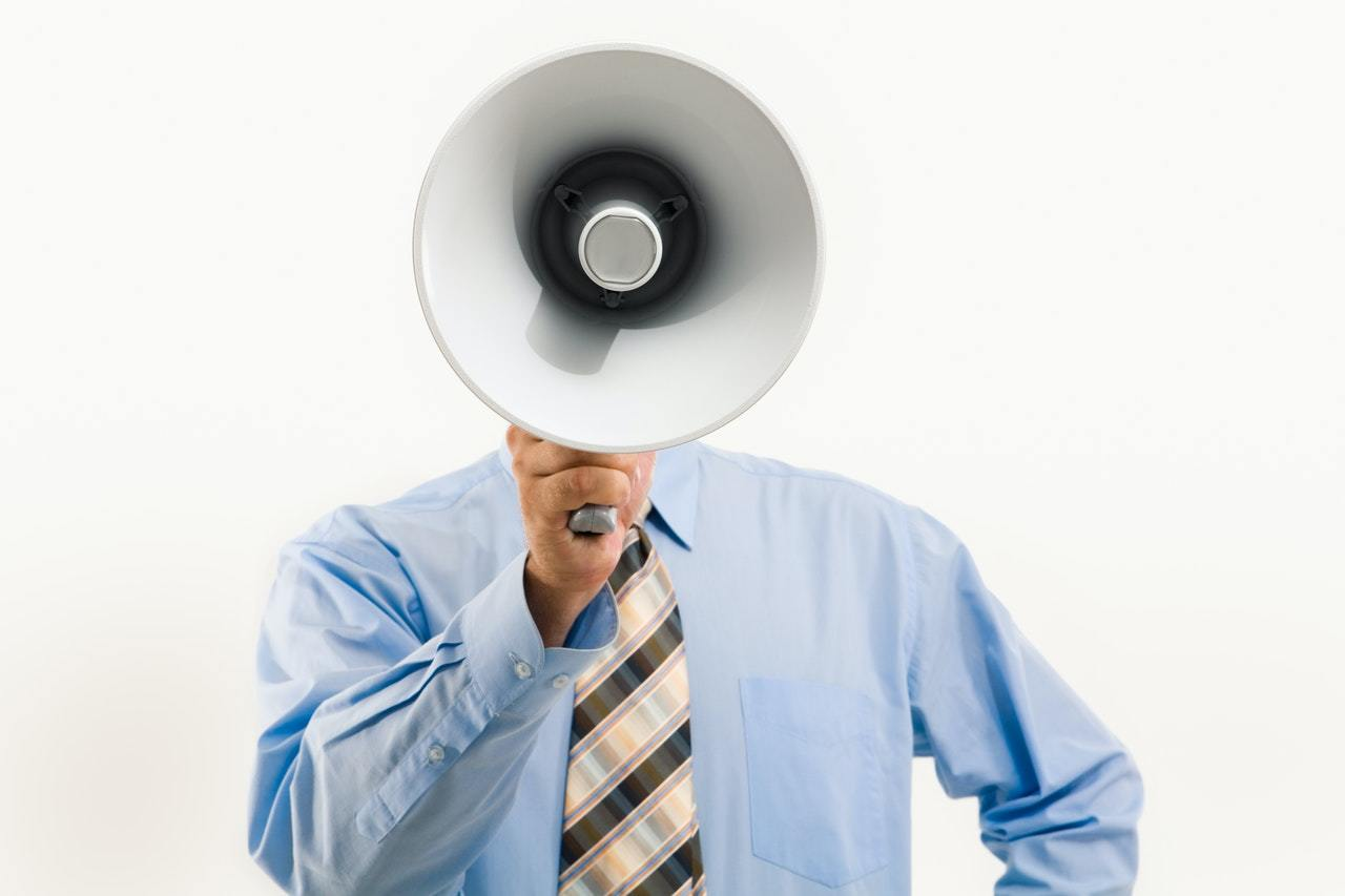 businessman shouting through a megaphone, representing bad leadership