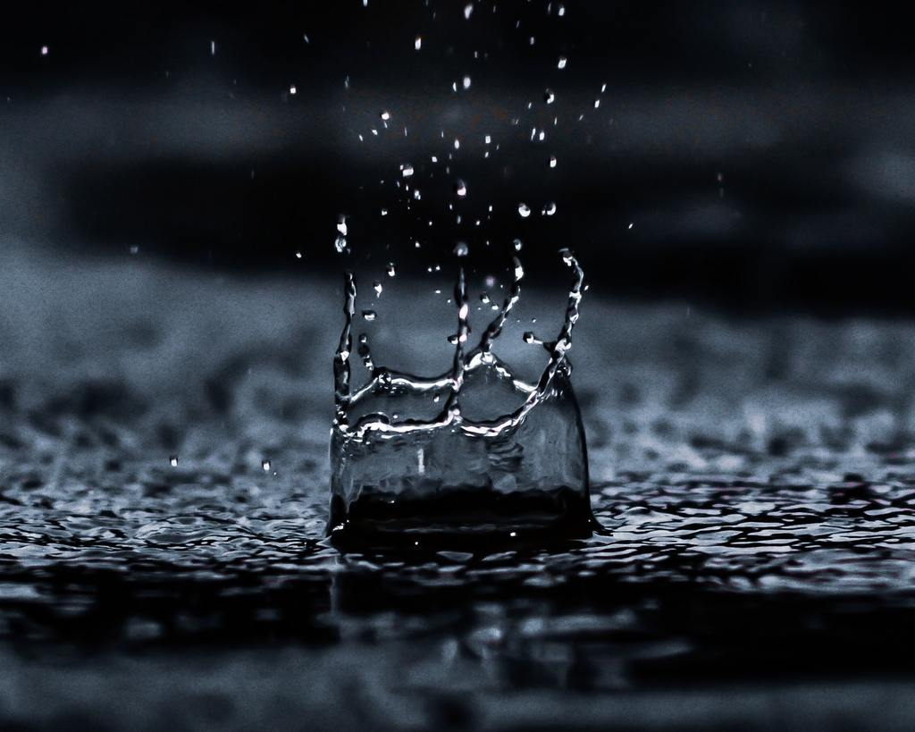 a water droplet splashes down, symbolizing liquid assets and alluding to illiquid assets