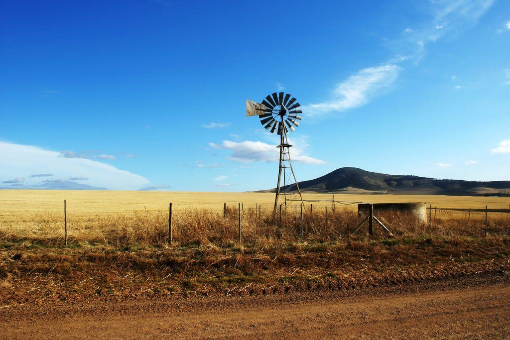 windmill on windswept plains represents buying farmland as an investment