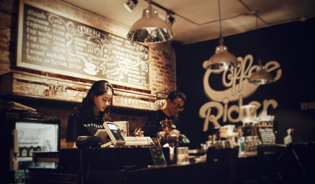 a coffee shop employee works at a register, representing