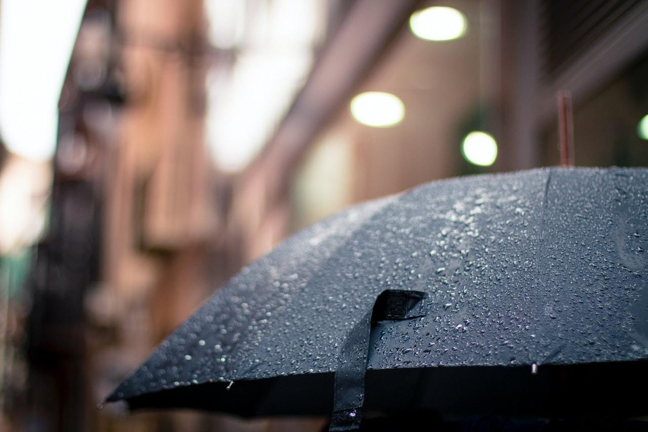raindrops on a black umbrella, symbolizing the need for a trade credit insurance policy