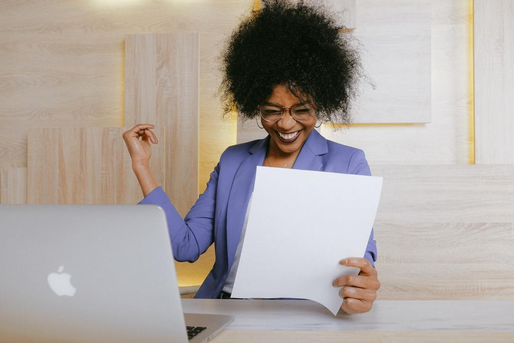 woman laughs with delight looking at her business plan, representing following your dreams