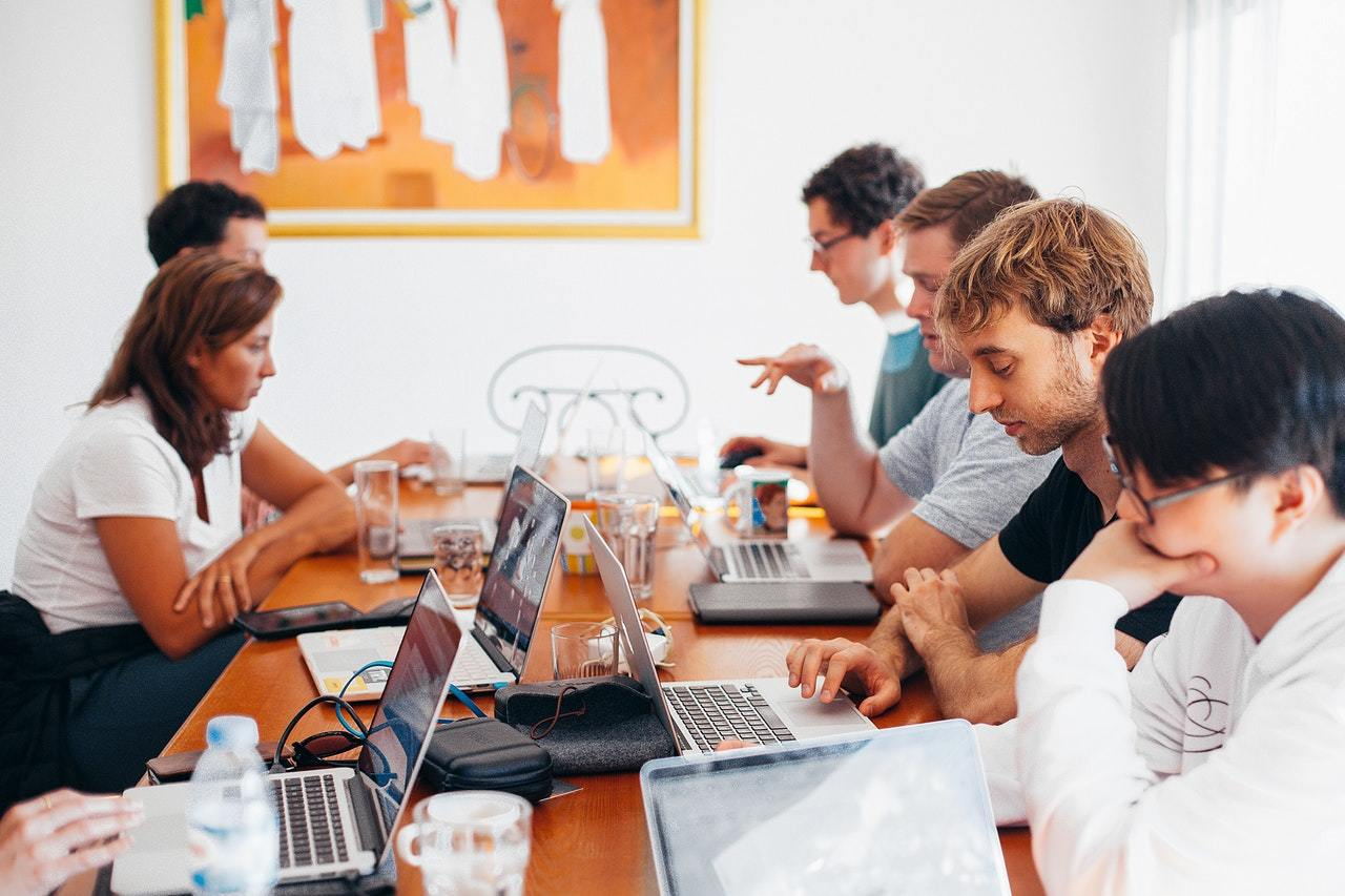 group of people sit with laptops at a conference table, representing a better marketing team in action